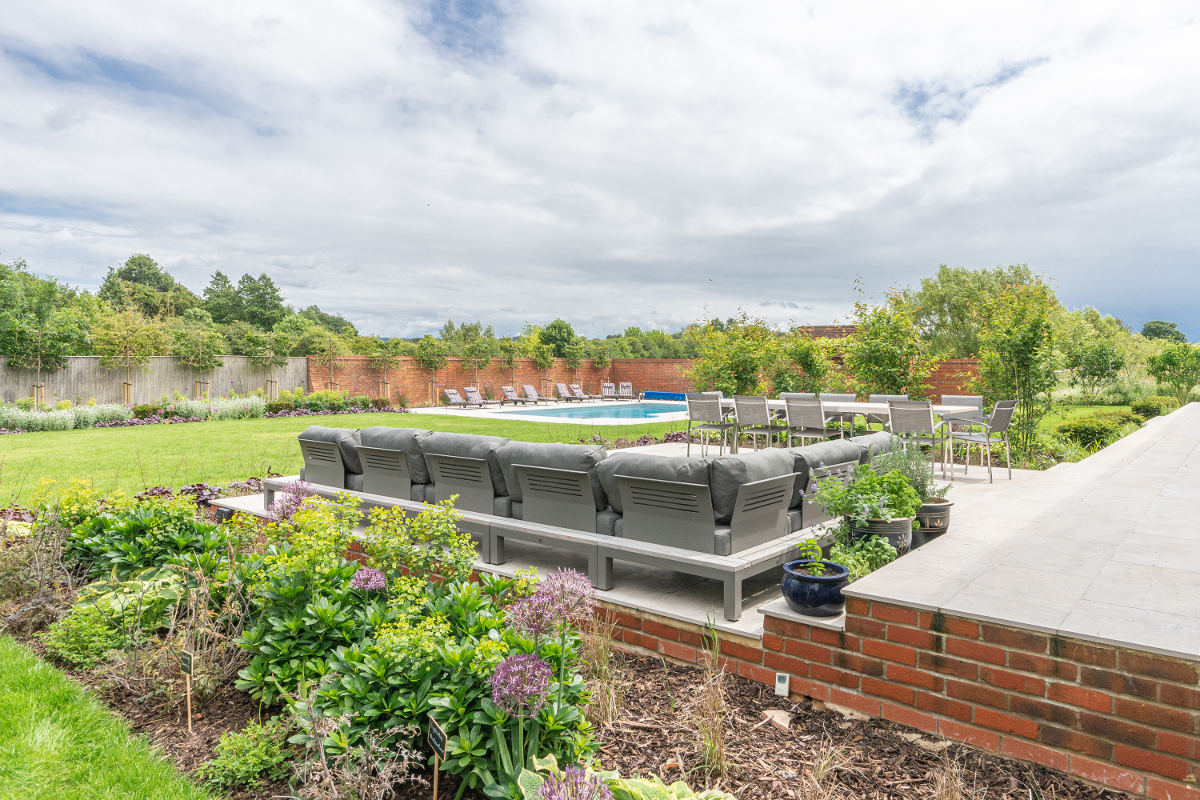 outdoor seating area overlooking garden and pool
